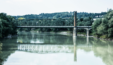 mirrored: Old railway bridge is mirrored in river, Passau, Lower Bavaria, Germany. Architectural theme. Travel destination. City of Three Rivers. Stock Photo