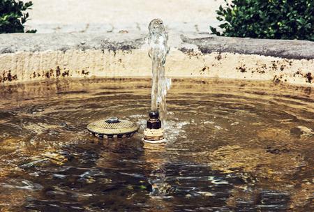 sprayed: Small fountain in the park. Garden decoration. Sprayed water. Drinking water.