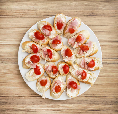 refreshments: Tasty canapes with butter, ham and cherry tomatoes. Full white plate. Food theme. Refreshments for guests. Catering theme.