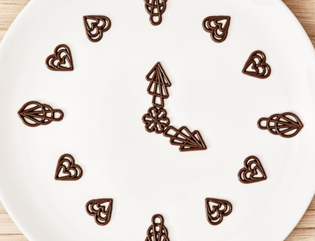 piped: Dark chocolate garnishes in the shape of the clock. Symbolic food. Chocolate clock. Measuring time. Time passage.