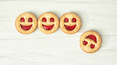 successes: Four round biscuits smiling faces, one of them falls down. Humorous food. Symbolic scene. Successes and failures.