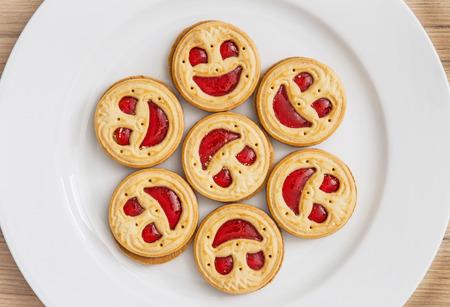 Sieben runde Kekse Gesichter auf dem weißen Teller lächelnd. Humorvoll Essen. Leckere Plätzchen. Gute Laune.