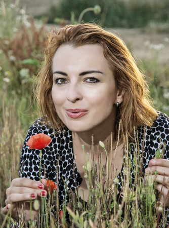 papaver rhoeas: Young beautiful caucasian woman posing in poppy flowers field. Summer time. Beauty, fashion and nature. Papaver rhoeas. Sexy woman.