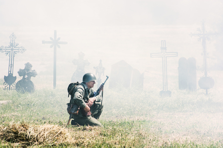 german soldier: NITRA, SLOVAK REPUBLIC - MAY 21: Reconstruction of the Second World War operations Between Red and German army, german soldier squats and patrols the cemetery on May 21, 2016 in Nitra, Slovak Republic.