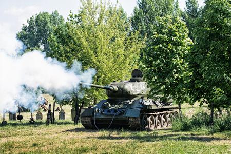 tanque de guerra: Nitra, ESLOVAQUIA - 21 de mayo: La reconstrucción de las operaciones de la Segunda Guerra Mundial entre el rojo y el ejército alemán, ruso tanque de guerra que dispara las posiciones enemigas de combate alemanas el 21 de mayo de 2016 en Nitra, Eslovaquia.