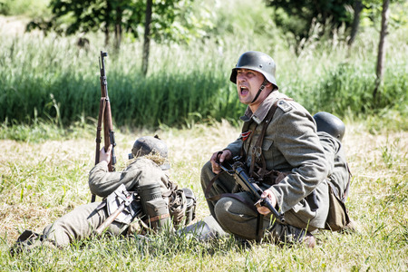 reinforce: NITRA, SLOVAK REPUBLIC - MAY 21: Reconstruction of the Second World War operations Between Red and German army, german noncommissioned officer Summons REINFORCE to the combat zone on May 21, 2016 in Nitra, Slovak Republic. Editorial