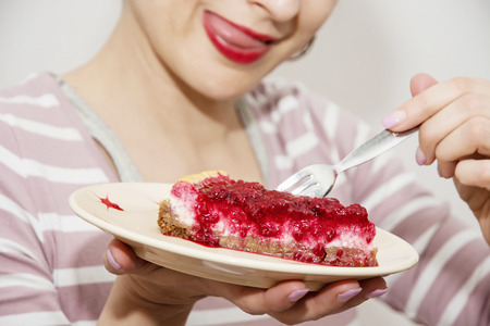Beautiful positive caucasian woman is tasting a piece of cheesecake with raspberries. Sweet food theme. Joyful woman. Cherry lips. Vibrant colors. Sexy woman. Food theme. Gourmand woman. Stockfoto