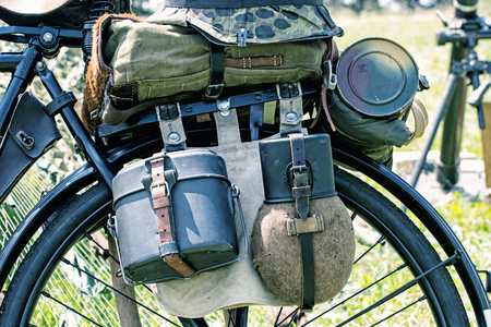 german soldier: Close up photo of old military bicycle with equipment. Backpack and containers for food and drink. Vintage scene. Retro transport. Equipment of german soldier in World War II.
