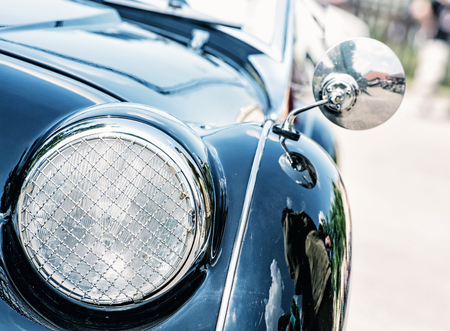 car model: Shiny blue vintage car. Detail view of the headlight. Retro car. Front light. Retro automobile scene. Circle headlamp.