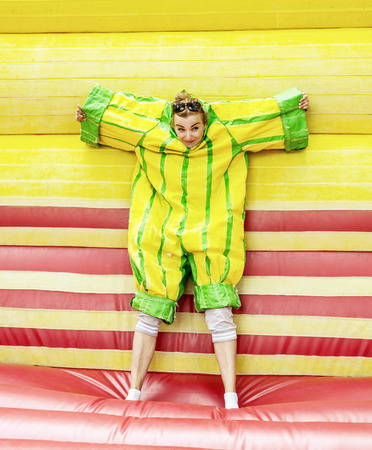 velcro: Joyful young caucasian woman in plastic dress in a bouncy castle imitates a fly on velcro wall. Inflatable attraction. Leisure activity. Crazy woman. Free time activities. Vertical composition. Fun park.