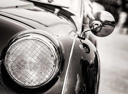 Shiny vintage car. Detail view of the headlight. Retro car. Black and white photo. Front light. Retro automobile scene. Circle headlamp.