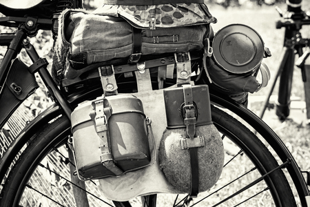 german soldier: Close up photo of old military bicycle with equipment. Backpack and containers for food and drink. Vintage scene. Black and white photo. Retro transport. Equipment of german soldier in World War II.