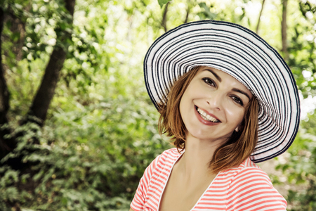 sunhat: Young caucasian woman with stylish sunhat posing in the forest. Beauty, fashion and nature. Positive emotions. Smiling face. Sun hat.