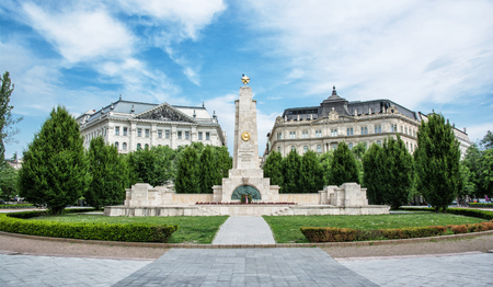 old  buildings: Soviet war memorial in Budapest, Hungary. Cultural heritage. Architectural theme. Historical object. Travel destination. Memorial place. Wide angle photo. Memorial, green trees and old buildings.
