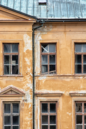 impaired: Old abandoned house in Banska Stiavnica, Slovak republic. Architectural theme. Ancient house. Ruin house. Cracked wall. Impaired statics. Old architecture. Broken windows. Stock Photo
