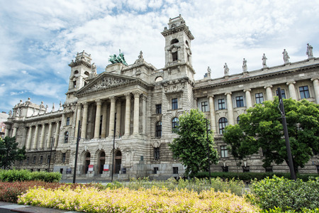 grandiose: Beautiful Ethnographic museum building and bed of seasonal flowers, Budapest, Hungary. Cultural heritage. Travel destination. Famous place. Tourism theme. Architectural theme. Kossuth square. Stock Photo