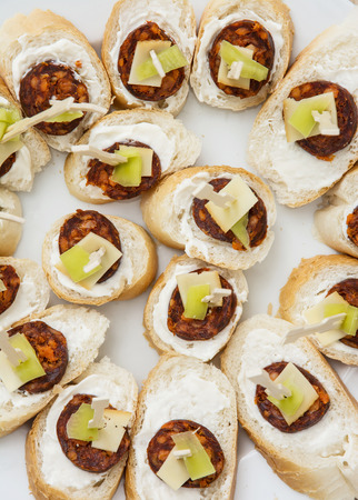 refreshments: Tasty canapes with butter, sausage, cheese and paprika. Food theme. Catering theme. Refreshments for guests. Sticks canapes. Open sandwiches. Stock Photo