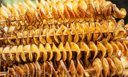 scalloped: Scalloped potatoes cut in the spiral form skewered on toothpicks. Food theme. Gourmet food. Delicious potatoes. International cuisine. Fried potatoes. Stock Photo