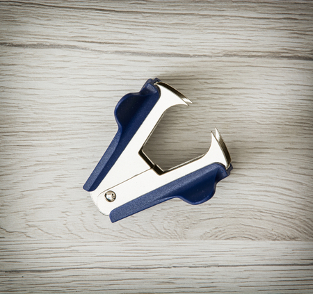 remover: One new staple remover on the wooden background. Office supply.