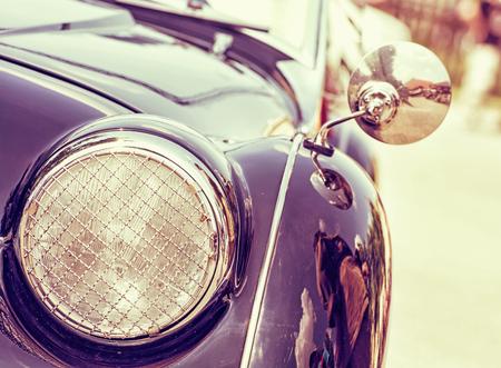 shiny car: Shiny vintage car. Retro photo filter. Detail view of the headlight. Retro car. Front light. Retro automobile scene. Circle headlamp. Stock Photo