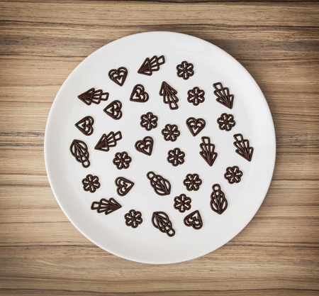 piped: Dark chocolate garnishes in the big plate. Sweet food. Symbolic shapes. Creative cuisine. Confection theme. Stock Photo
