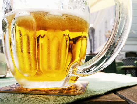 alcoholic drink: Glass of light beer. Tasty refreshment. Alcoholic drink. Glass cup on the tray. Lager beer. Stock Photo