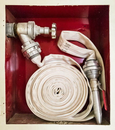 Fire cock with stacked hose. Water tap. Modern system. Iron hydrant valve. Socket for connection of fire hose. Stock Photo