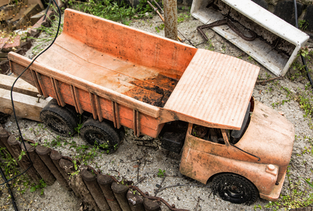 Dirty children truck at the garden. Outdoor toy. Retro toy. Leisure activity. Preschool game theme. Nobody scene. Stock Photo