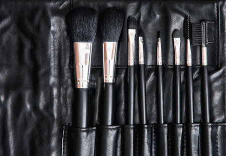 leather bag: Set of cosmetic brushes in black leather bag. Beauty and fashion. Beauty salon. Skin care. Makeup brush. Stock Photo