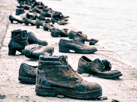 Shoes on the Danube bank is a memorial in Budapest, Hungary. Blue photo filter. Shoes monument. Place of reverence. Cultural heritage. Symbolic object.