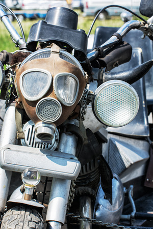 handlebars: Detail of veteran motorbike with symbolic gas mask. Meeting bikers. Front view. Handlebars and headlight. Exhibitionism theme. Stock Photo