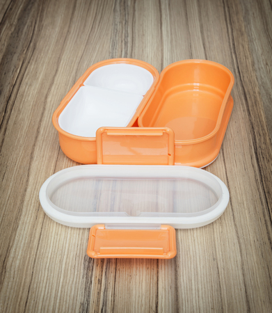 food storage: Orange folding plastic box for food storage on the wooden background. Open box. Kitchen equipment. Set of boxes.