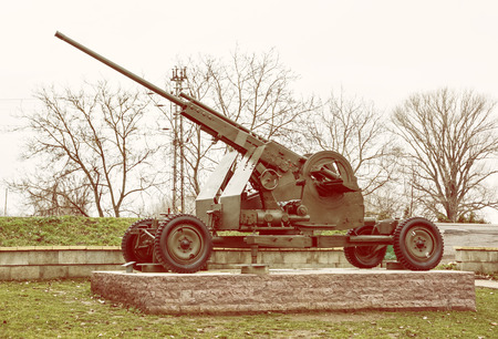 militarily: Anti-aircraft machine gun of the World war II. War industry. Biggest war campaign of 20th century. Yellow photo filter. Weapons theme. Exposed artillery. Editorial