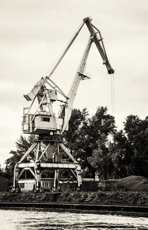 vertical composition: Crane in cargo port translating coal. Industrial scene. Black and white photo. Big port-crane. Vertical composition.