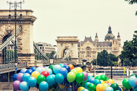 Famous Chain bridge, Saint Stephens basilica and colorful balloons in Budapest, Hungary. Cultural heritage. Entertainment event. Travel destination. Retro photo filter. Tourism theme. Architectural theme.