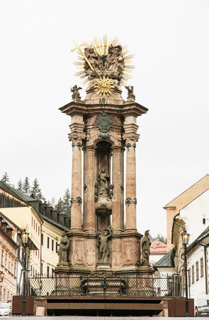 vertical composition: Historical Trinity square with monumental plague column in Banska Stiavnica, Slovak republic. Cultural heritage. Religious architecture. Travel destination. Vertical composition.