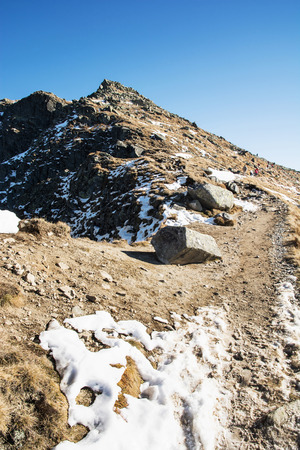 mountainy: Footpath leading up the peak Dumbier, Low Tatras, Slovakia. Hiking theme. Snow and rocks. Mountains scene. Vertical composition. Stock Photo