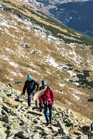 Young woman with son on the mountain footpath leading up the peak Dumbier, Low Tatras, Slovak republic. Hiking theme. Mountains scene. Travelers on the stoned sidewalk.