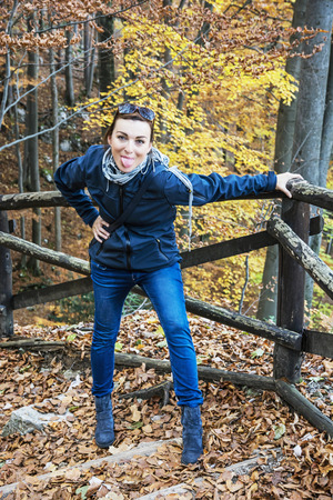 vibrant colors fun: Crazy young woman makes fun in the autumn forest. Hiking theme. Beauty and fashion. Positive emotions. Vertical composition. Seasonal natural scene. Vibrant colors.
