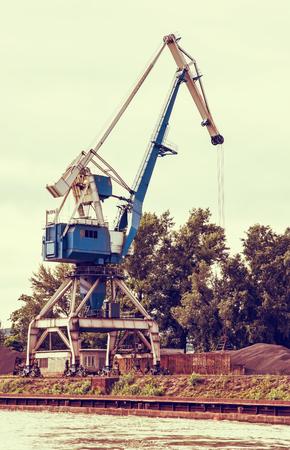 vertical composition: Blue crane in cargo port translating coal. Industrial scene. Retro photo filter. Vertical composition. Stock Photo