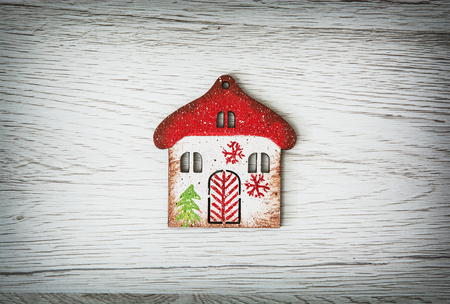 vibrant cottage: Little decorative house on the wooden background. Symbolic object. Winter decoration.