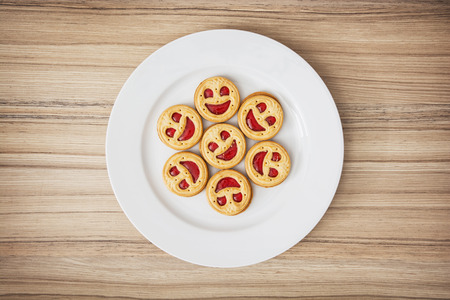 Seven round biscuits smiling faces on the white plate. Good mood. Humorous food. Tasty cookies.