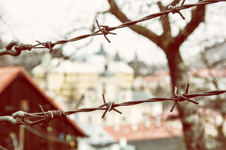 private property: Barbed wire fence in old town Banska Stiavnica, Slovak republic. Security theme. Yellow photo filter. Travelling in Europe. Private property. Stock Photo