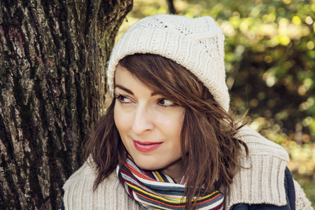 face in tree bark: Young youful caucasian woman posing in autumn nature. Seasonal fashion. Female portrait. Vibrant colors. Stock Photo