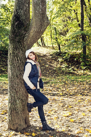 beech tree beech: Beautiful young positive woman posing under the beech tree in autumn nature. Vibrant colors. Seasonal fashion. Vertical composition. Stock Photo