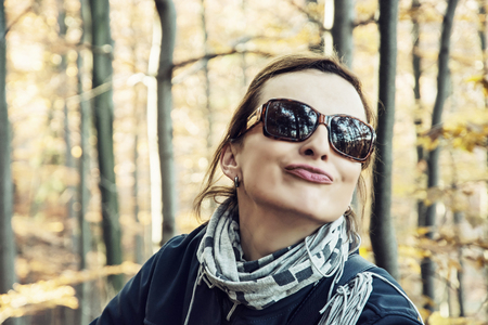 changing seasons: Young caucasian woman in the autumn forest makes crazy face. Seasonal natural scene. Female portrait.