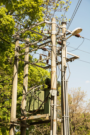 electricity pylon: Electric pole with the transformer in the forest. Electricity pylon with ceramic fuses. Power industry theme. Stock Photo