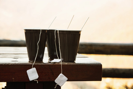 mountainy: Three hot tea cups in outdoors. Refreshment for hike. Drinking in nature. Hiking theme. Stock Photo