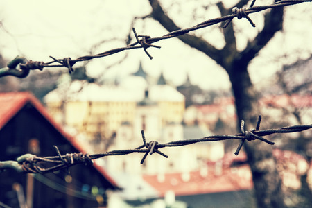 private property: Barbed wire fence in old town Banska Stiavnica, Slovak republic. Security theme. Retro photo filter. Travelling in Europe. Private property.