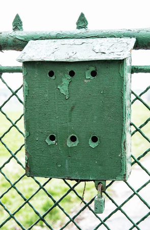 mail delivery: Old green metallic mailbox on the fence. Mail delivery. Retro object. Vertical composition.